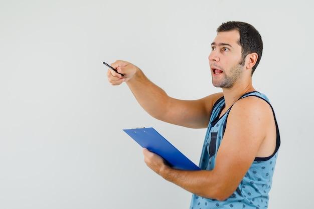 クリップボードを持って、向こうを指して、好奇心をそそる青い一重項の若い男。