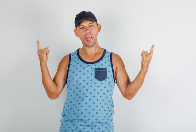 キャップを指で身振りで示すことと舌を見せて幸せそうに見えて青い一重項の若い男