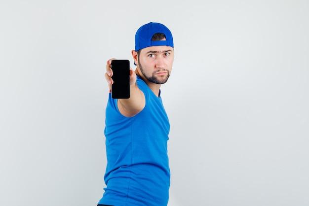 Молодой человек в синей футболке и кепке держит мобильный телефон и выглядит серьезно
