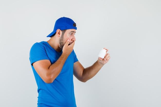 青いtシャツとキャップの若い男が薬瓶を保持し、驚いて見える