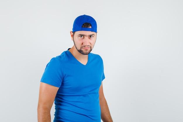 青いtシャツとキャップの若い男がカメラを注意深く見て自信を持って見える