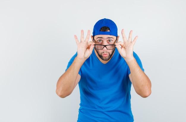 青いtシャツとキャップの若い男がメガネを注意深く見ています
