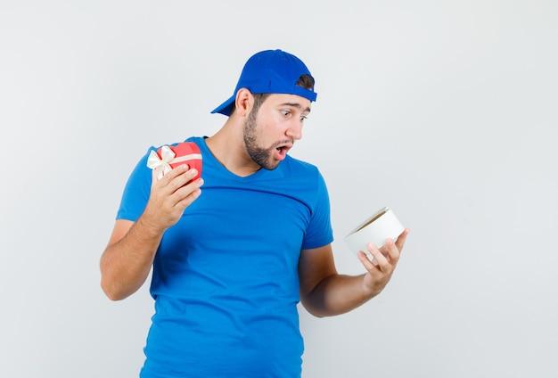 青いtシャツとキャップの若い男がギフトボックスを見て驚いて見える