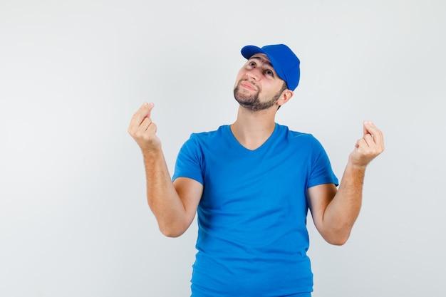 青いtシャツとキャップを身に着けている若い男は、指で身振りで示し、希望を持って見ながら見上げる