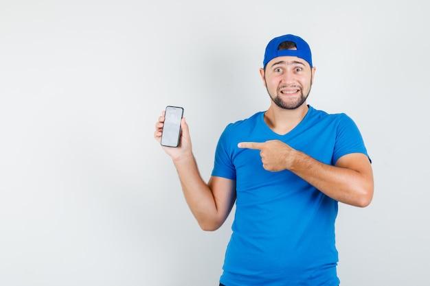 Молодой человек в синей футболке и кепке указывает на мобильный телефон и выглядит веселым