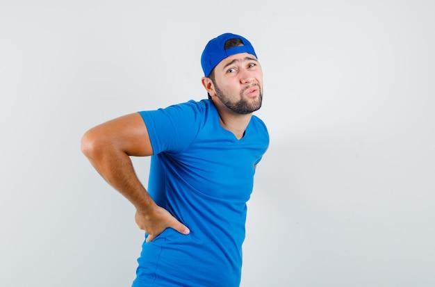 Молодой человек в синей футболке и кепке страдает от болей в спине и выглядит усталым