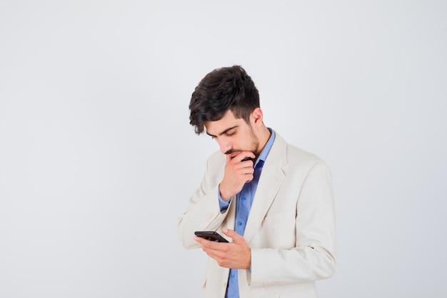 青いtシャツと白いスーツのジャケットを着た若い男がスマートフォンを持って考えポーズで立って物思いにふける