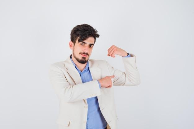 青いtシャツと白いスーツのジャケットの若い男は筋肉を示し、真剣に見えます