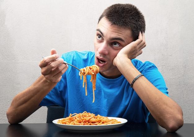Молодой человек в синей футболке ест спагетти
