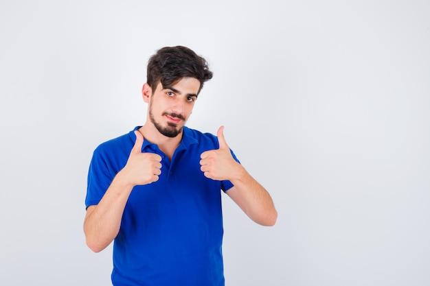 파란색 티셔츠에 젊은 남자가 두 손으로 엄지 손가락을 보이고 행복해 보입니다.