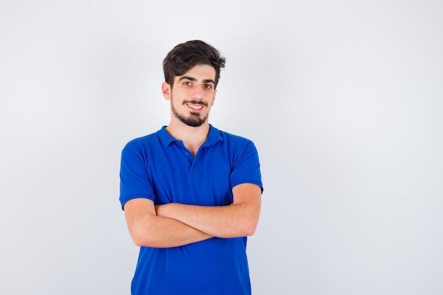 Молодой человек в синей футболке стоит, скрестив руки, и выглядит серьезным