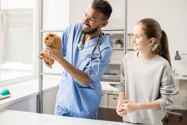 ペットの世話について少女に相談しながらブロンモルモットを保持している獣医の青い制服を着た若い男