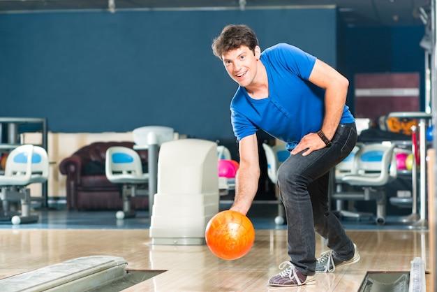 楽しんでいるボウリング場の若い男、テンピン路地の前でボウリング球をしているスポーティな男
