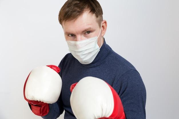 Молодой человек в боксерских перчатках и медицинской маске на лице в позе готов нанести удар на белом фоне