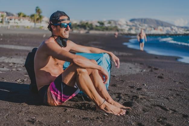Молодой человек в кепке, очках и одежде для серфинга смотрит на море с маской короны