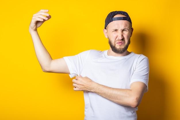 黄色の背景に汗と臭い脇の下の帽子とtシャツの若い男。