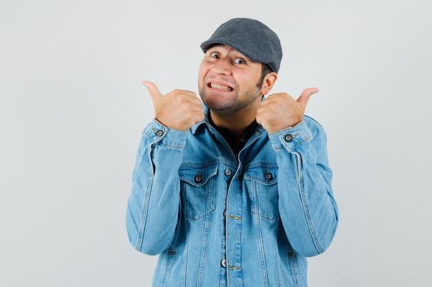 Молодой человек в кепке, футболке, куртке показывает двойные пальцы вверх и выглядит веселым