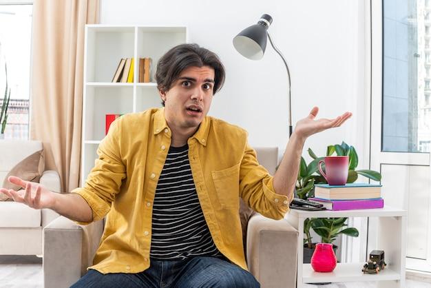 Молодой человек в повседневной одежде смущен, разводя руками в стороны, сидя на стуле в светлой гостиной