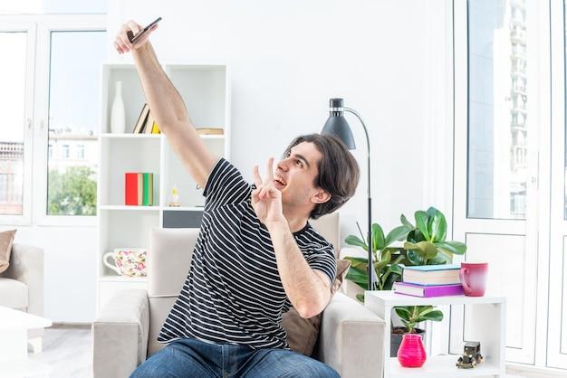 밝은 거실에서 의자에 앉아 스마트 폰 행복하고 긍정적 인 보여주는 v 기호를 사용하여 셀카를하고 캐주얼 옷을 입은 젊은 남자