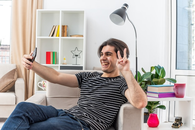밝은 거실에서 의자에 앉아 행복하고 쾌활한 v 기호를 보여주는 스마트 폰을 사용하여 셀카를하고 캐주얼 옷을 입은 젊은 남자