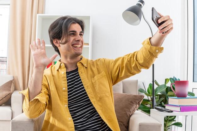 밝은 거실의 의자에 광범위하게 앉아 행복하고 쾌활한 손으로 흔들며 스마트 폰을 사용하여 셀카를하고 캐주얼 옷을 입은 젊은 남자