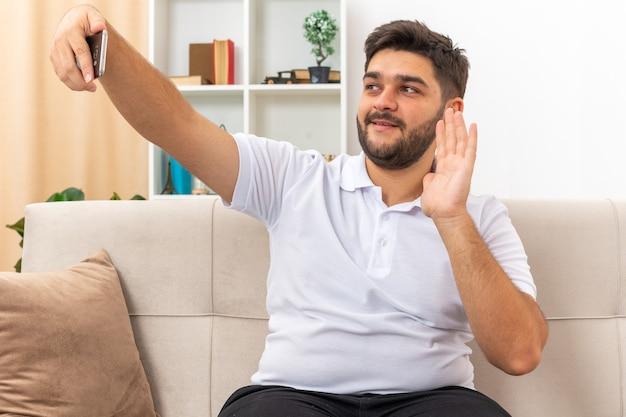 明るいリビング ルームのソファに座って家で週末を過ごす陽気な笑顔で手を振るスマートフォンを使用してカジュアルな服装の若い男
