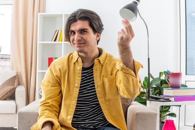 가벼운 거실의 의자에 앉아 불만과 분노에 손으로 몸짓을하는 캐주얼 옷을 입은 젊은 남자