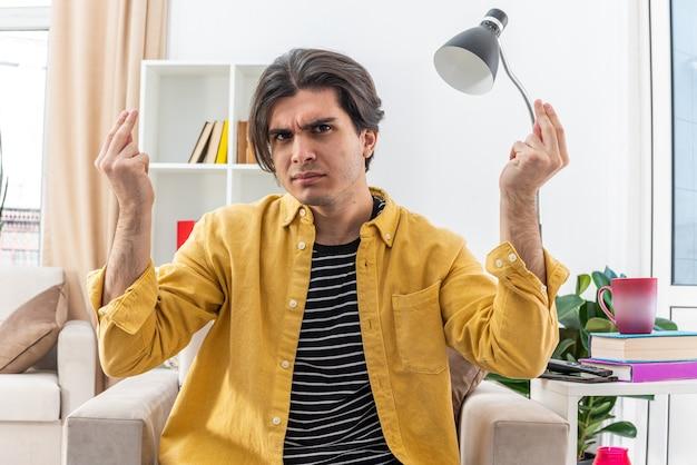 明るいリビング ルームの椅子に座って不愉快と憤慨の手で身振りで示すカジュアルな服装の若い男