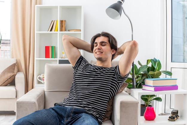 明るいリビング ルームの椅子に座って週末を過ごす、幸せでポジティブなリラックスしたカジュアルな服装の若い男