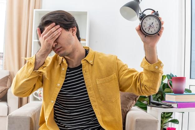 Молодой человек в повседневной одежде держит будильник, прикрывая глаза рукой, уставшей и скучающей, сидя на стуле в светлой гостиной