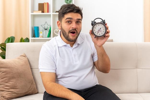 Молодой человек в повседневной одежде держит будильник, счастливый и удивленный, сидя на диване в светлой гостиной