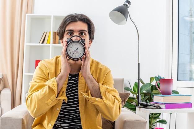 Молодой человек в повседневной одежде держит будильник перед лицом и выглядит обеспокоенным, сидя на стуле в светлой гостиной
