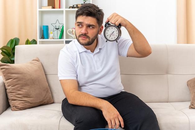 Молодой человек в повседневной одежде держит будильник со скептическим выражением лица, сидя на диване в светлой гостиной