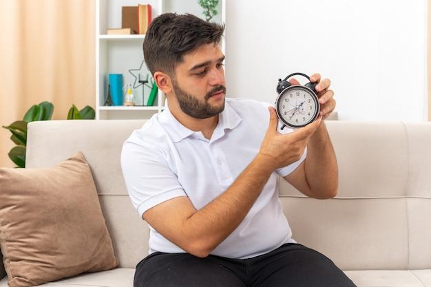 Молодой человек в повседневной одежде держит будильник, глядя на него с серьезным лицом, сидя на диване в светлой гостиной