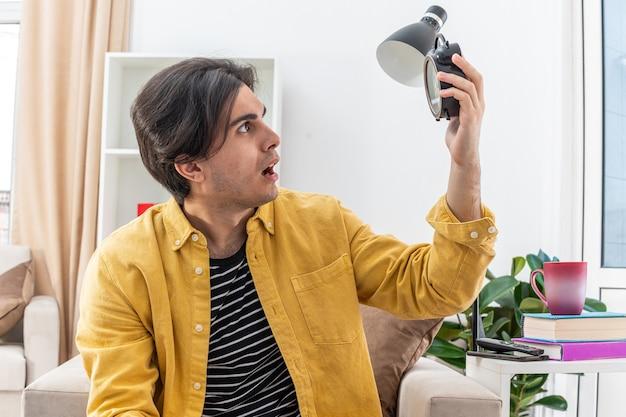 Молодой человек в повседневной одежде держит будильник, глядя на него взволнованно, сидя на стуле в светлой гостиной
