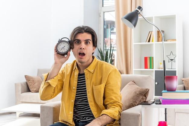 Молодой человек в повседневной одежде держит будильник с удивленным видом, сидя на стуле в светлой гостиной