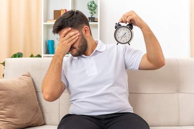Молодой человек в повседневной одежде с будильником выглядит усталым и скучающим, прикрывая глаза рукой, сидя на диване в светлой гостиной