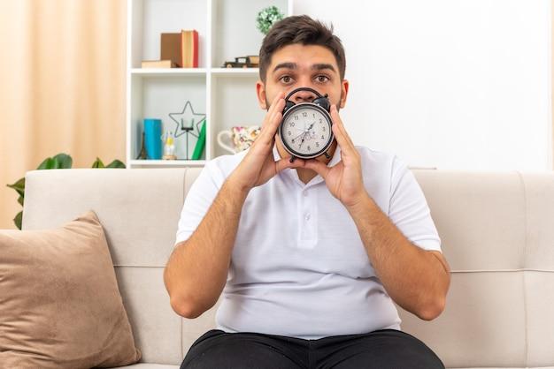 Молодой человек в повседневной одежде с будильником и взволнованным видом сидит на диване в светлой гостиной