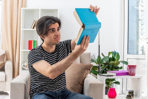 Молодой человек в повседневной одежде держит книгу, глядя на нее с грустным выражением лица, сидя на стуле в светлой гостиной