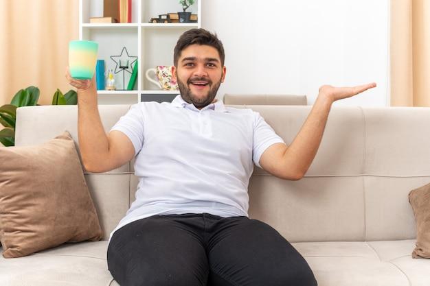 Молодой человек в повседневной одежде, держащий чашку, выглядит счастливым и веселым, раскинув руку в сторону, сидя на диване в светлой гостиной