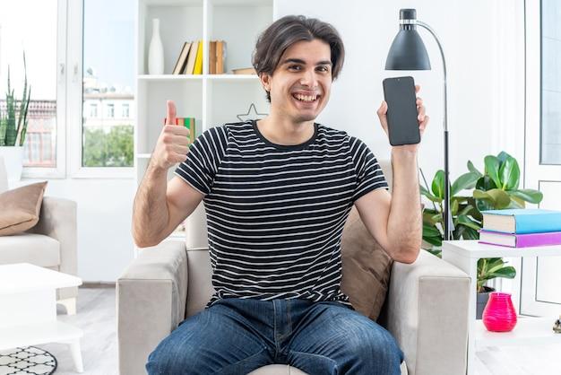 スマートフォンを持ったカジュアルな服装の若い男が、明るいリビング ルームの椅子に大きく座って笑顔を見せる幸せで陽気な顔を見せる