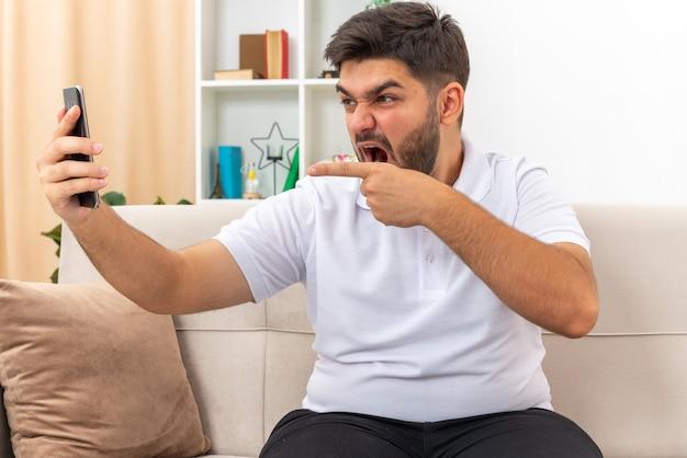 밝은 거실에서 소파에 앉아 집에서 주말을 보내는 공격적인 표현으로 화상 통화를 갖는 스마트 폰을 들고 캐주얼 옷을 입은 젊은 남자