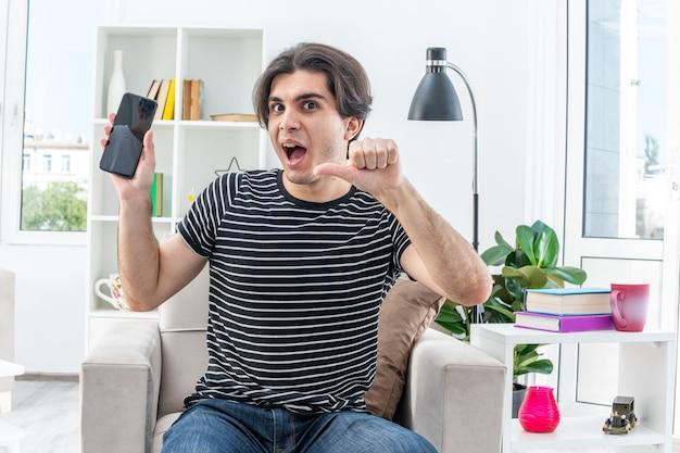 밝은 거실의 의자에 앉아 엄지 손가락을 보여주는 행복하고 흥분된 스마트 폰을 들고 캐주얼 옷을 입은 젊은 남자