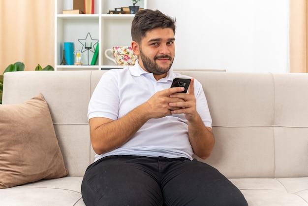 밝은 거실에서 소파에 앉아 행복하고 긍정적 인 미소 자신감을 찾고 스마트 폰을 들고 캐주얼 옷에 젊은 남자