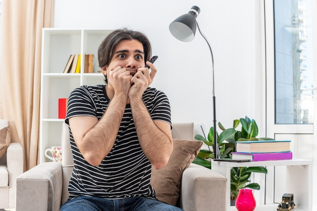 Tv 리모컨을 들고 캐주얼 옷을 입은 젊은 남자가 밝은 거실의 의자에 앉아 스트레스를 받고 무서워하는 손톱을 무서워합니다.