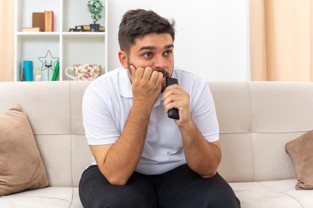 Молодой человек в повседневной одежде держит телевизор и смотрит телевизор, выглядит напряженным и нервным, проводя выходные дома, сидя на диване в светлой гостиной