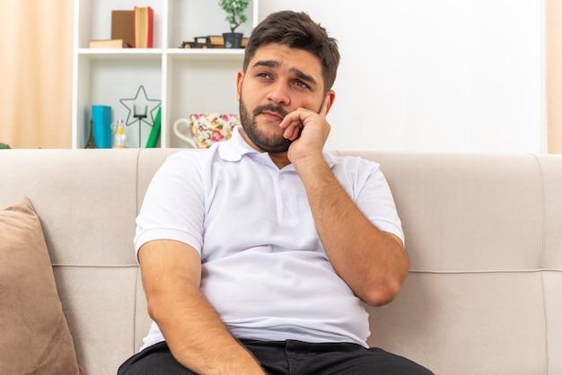Молодой человек в повседневной одежде озадаченно смотрит в сторону, сидя на диване в светлой гостиной