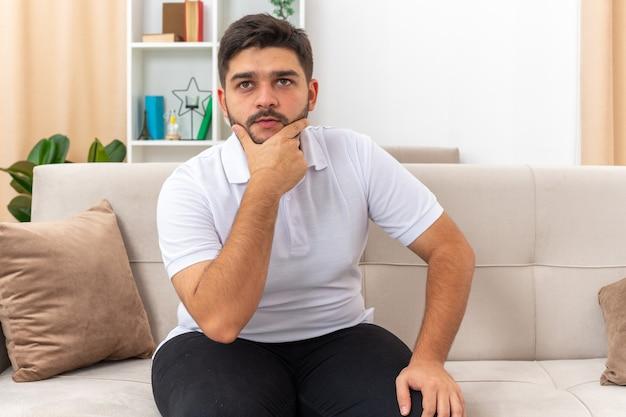 Молодой человек в повседневной одежде, озадаченный, положив руку на подбородок, сидит на диване в светлой гостиной