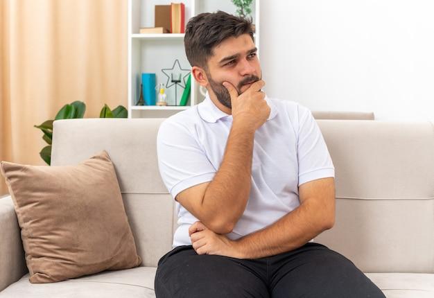 Молодой человек в повседневной одежде смотрит в сторону с задумчивым выражением лица, положив руку на подбородок, думает, сидя на диване в светлой гостиной