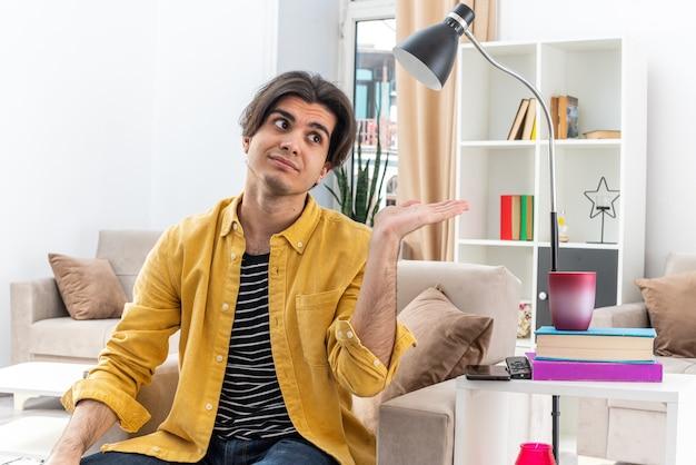 Молодой человек в повседневной одежде смотрит в сторону с улыбкой на лице, представляя что-то рукой, сидящей на стуле в светлой гостиной